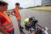 Een student repareert een euvel aan de fiets. Op een weg in Delft worden de eerste meters afgelegd met de nieuwe recordfiets, de VeloX 8. In september wil het Human Power Team Delft en Amsterdam, dat bestaat uit studenten van de TU Delft en de VU Amsterdam, tijdens de World Human Powered Speed Challenge in Nevada een poging doen het wereldrecord snelfietsen voor vrouwen te verbreken met de VeloX 8, een gestroomlijnde ligfiets. Het record is met 121,81 km/h sinds 2010 in handen van de Francaise Barbara Buatois. De Canadees Todd Reichert is de snelste man met 144,17 km/h sinds 2016.<br /> <br /> At a road in Delft the team tests the VeloX 8 for the first time. With the VeloX 8, a special recumbent bike, the Human Power Team Delft and Amsterdam, consisting of students of the TU Delft and the VU Amsterdam, also wants to set a new woman's world record cycling in September at the World Human Powered Speed Challenge in Nevada. The current speed record is 121,81 km/h, set in 2010 by Barbara Buatois. The fastest man is Todd Reichert with 144,17 km/h.