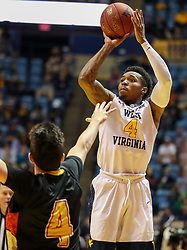 Dec 16, 2017; Morgantown, WV, USA; West Virginia Mountaineers guard Daxter Miles Jr. (4) shoots over Wheeling Jesuit Cardinals guard Preston Boswell (4) during the second half at WVU Coliseum. Mandatory Credit: Ben Queen-USA TODAY Sports
