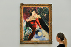 "© Licensed to London News Pictures. 06/10/2017. London, UK. A staff member views ""Les Amoureux"", 1928, by Marc Chagall at a preview at Sotheby's in New Bond Street of contemporary, impressionist and modern art works to be auctioned in New York in November 2017 Photo credit : Stephen Chung/LNP"