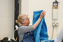 © Licensed to London News Pictures. 21/04/2020. Dukinfield, UK.   A woman folds medical clothing as staff at Tibard begin working around the clock an order of 5,000 units of nurses uniforms (scrubs) for NHS workers per week in Dukinfield , owing to growing demand during the COVID-19 pandemic. The factory typically manufactures uniforms for the catering industry.  Photo credit: Ioannis Alexopoulos /LNPLNP