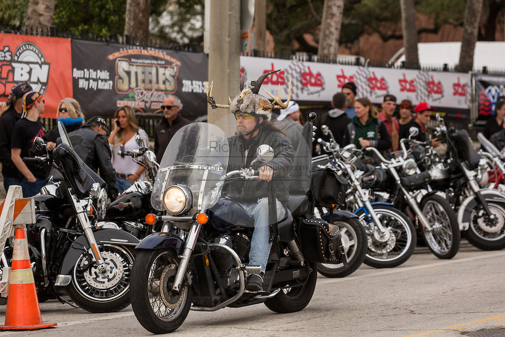 A biker wearing horns on his helmet cruises down Main Street during the 74th Annual Daytona Bike Week March 7, 2015 in Daytona Beach, Florida.