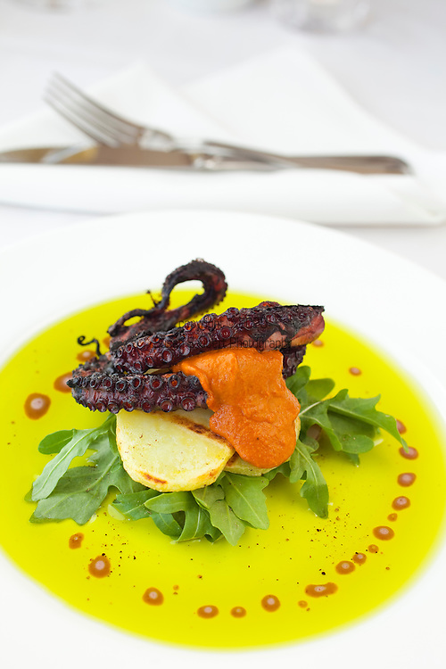 Alloro Restaurant, a fine dining restaurant located in Old Town Bandon, Oregon. Grilled Octopus with Spanish style romesco sauce, yukon gold potatoes, arugula