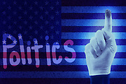 "A white gloved hand with a dirty index finger has spelled the work ""politics"" in the dust covering an American flag.Black light"