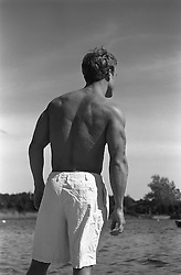 Back of a shirtless man looking at water in East Hampton,NY