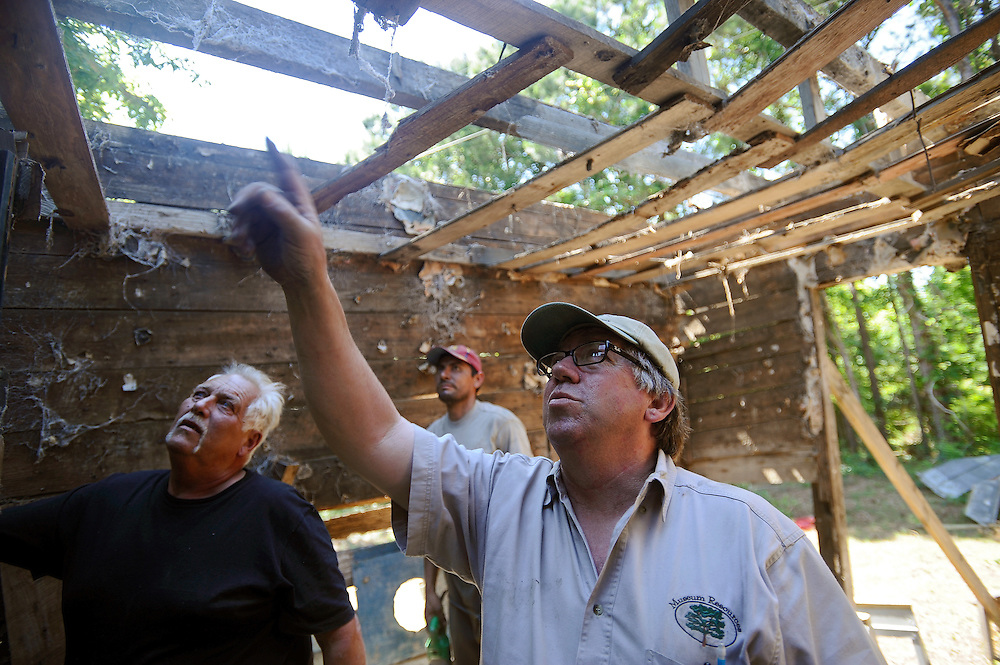 Kerry Shackelford, project site contractor for Museum Resources, Construction and Mill Work, Inc., directs his foreman Larry Francis, right, how he wants to dismantle the roof joists of an 18th-century slave cabin for the Smithsonian Institution. The cabin is only cabin that remains of the string of cabins built in the 1940s or 50s at the Bailey plantation of Point of Pines on Edisto Island, South Carolina. After it is dismantled the cabin will be reassembled at the Smithsonian's new National Museum of African American History and Culture in Washington, D.C. (Stephen Morton for The New York Times)