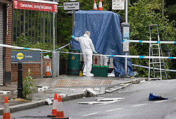 © Licensed to London News Pictures. 10/06/2020. Leatherhead, UK. Forensics officers cover a bust stop in Leatherhead, Surrey after a body was found. Officers were called to North Street in Leatherhead shortly after 6am this morning following the discovery of a man's body. Enquiries are ongoing at a number of locations in the area. Local reports say that the body may have been found in a block of flats off the High Street. Photo credit: Peter Macdiarmid/LNP