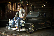 Actor John Schneider sits on the hood of an old Chevrolet used as a prop for films. It's parked near the entrance to a live music stage located in a wooden barn at Schneider's studio in Holden, Louisiana.  (Photo by Chris Granger, NOLA.com | The Times-Picayune)