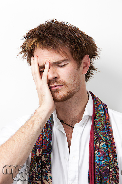Sad young man with hand on face against white background