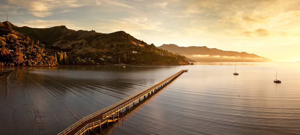 Govenor's Bay Jetty at sunrise with two yachts moored and Lyttelton Harbour in background.  New Zealand.