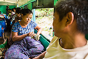 15 JUNE 2013 - YANGON, MYANMAR:  A woman counts her Kyats (Myanmar currency) while she rides the Yangon Circular Train with her husband. Yangon Circular Railway is the local commuter rail network that serves the Yangon metropolitan area. Operated by Myanmar Railways, the 45.9-kilometre (28.5mi) 39-station loop system connects satellite towns and suburban areas to the city. The railway has about 200 coaches, runs 20 times and sells 100,000 to 150,000 tickets daily. The loop, which takes about three hours to complete, is a popular for tourists to see a cross section of life in Yangon. The trains from 3:45 am to 10:15 pm daily. The cost of a ticket for a distance of 15 miles is ten kyats (~nine US cents), and that for over 15 miles is twenty kyats (~18 US cents). Foreigners pay 1 USD (Kyat not accepted), regardless of the length of the journey.     PHOTO BY JACK KURTZ