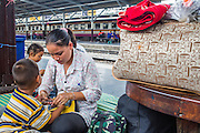 17 APRIL 2013 - BANGKOK, THAILAND:  A family in Hua Lamphong Train Station in Bangkok waits to catch a train back to their province after Songkran. Songkran, the traditional Thai New Year, is the busiest time of the year for Thai domestic travel. Many people in Bangkok return to their home provinces for the holiday and some people in the provinces travel to Bangkok for the holiday. Songkran, usually a three day holiday, was five days this year because the official days on the weekend. Trains and buses coming into Bangkok were reported to be fully booked and the State Railway of Thailand added extra trains and carriages to accommodate the crowds.   PHOTO BY JACK KURTZ