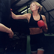 A woman wearing boxing gloves punching a punch bag in a gym