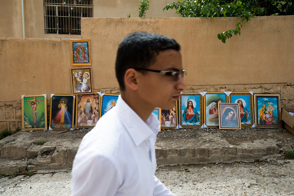 A Christian boy walks past religious icons being sold at the entrance to the Rabban Beya Temple. The 4th century Christian monastery is a series of monastic caves carved into a mountain high above the Shaqlawa valley and an important pilgrimage site for the Assyrian community. Shaqlawa, Iraq. 22/04/2014.