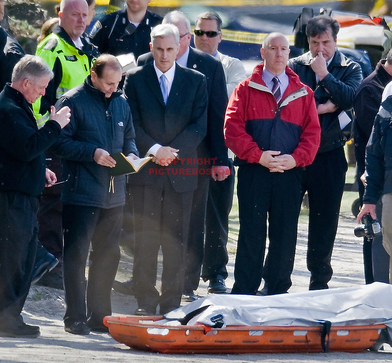 From left, Father Don Macmillan and Father Tony Penna, two chaplains from Boston College ,pray over a body (in orange sled) that was recovered this morning in the Reservoir nearest Cleveland Circle. Third from left is Boston College spokesperson Jack Dunn and others include police investigators. Staff Photo by Mark Garfinkel  .