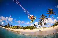 Professional kiteboarder Clinton Bolton does a jump in front of a pristine white sand beach and palm trees in Barbuda, Caribbean.
