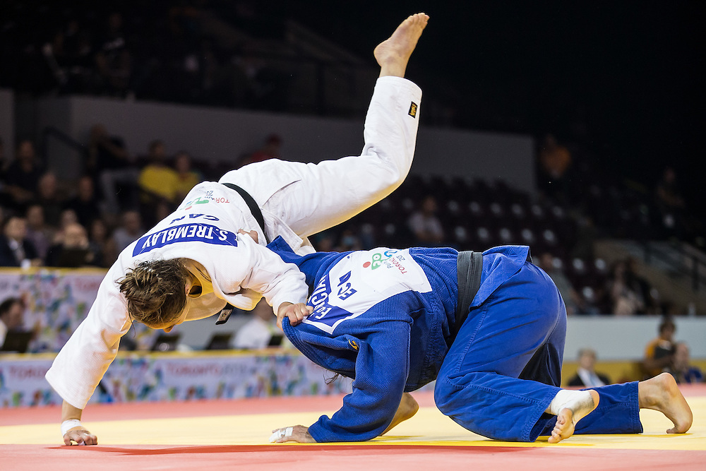 Stefanie Tremblay (L) of Canada is thrown by Estefania Garcia of Ecuador during their gold medal contest in the women's judo -63kg class at the 2015 Pan American Games in Toronto, Canada, July 13,  2015. Garcia went on town the gold medal defeating Tremblay.  AFP PHOTO/GEOFF ROBINS