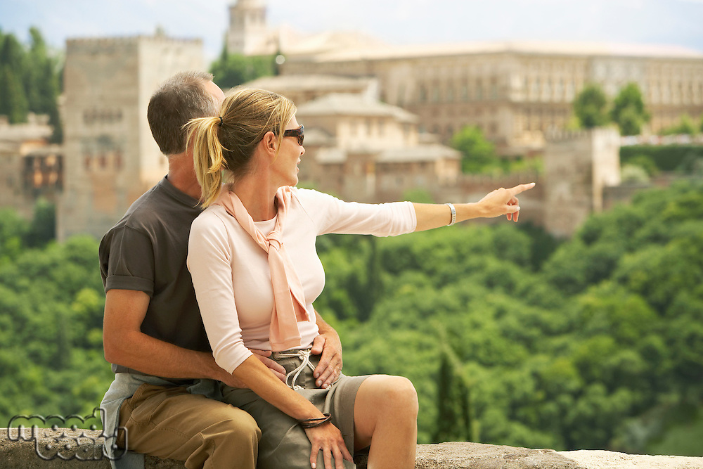 Tourist Couple sitting on Wall in Granada Spain looking and pointing at view