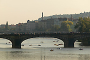 Czeck Republic - Prague, Rowboats and paddleboats cruise the Vltava river in the center of the city where the the Legií bridge arches overhead, view south from the Charles bridge