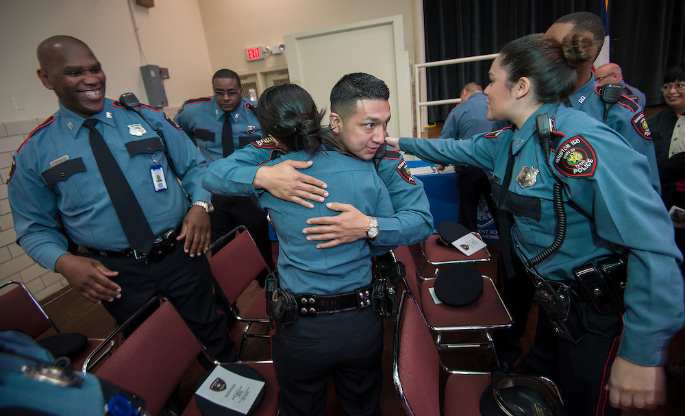 "Minhnguyet ""Nicky"" Tran, center, gets a hug from a fellow officer after a swearing-in ceremony for new officers at the Houston ISD Police Department, March 3, 2014."