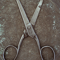 Vintage steel kitchen scissors lying wide open on tarnished metal