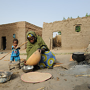One of Adama Garba's malnourished twin girls, Hassana and Oussaina Souley (14 months), plays with firewood while her mother prepares the evening meal at their home in the village of Nakaidabo in the Tessaoua region of Niger. This evening Adama has only a few handfuls of beans and a pinch of salt to feed her family of seven.