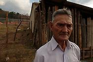 San Rafael Las FLores, Santa Rosa, Guatemala  Clodoveo RodrÌguez, de 78 anos, ha vivido toda la vida en su terreno en la comunidad de Los Planes.  Se niega a salir.  En el trasfondo, un edificio perteneciente a la empresa Minera San Rafael.PHOTO: Graham Charles Hunt/IMAGENES LIBRES