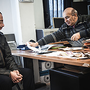 Mohamed observe les effets personnels de son frère Bilal que Angelo dépose sur la table, dans le bureau du G.I.C.I.C. (Groupe Interforces Contre l'Immigration Clandestine)
