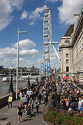Tourist crowds walk along London's Southbank beneath the Millennium Wheel.