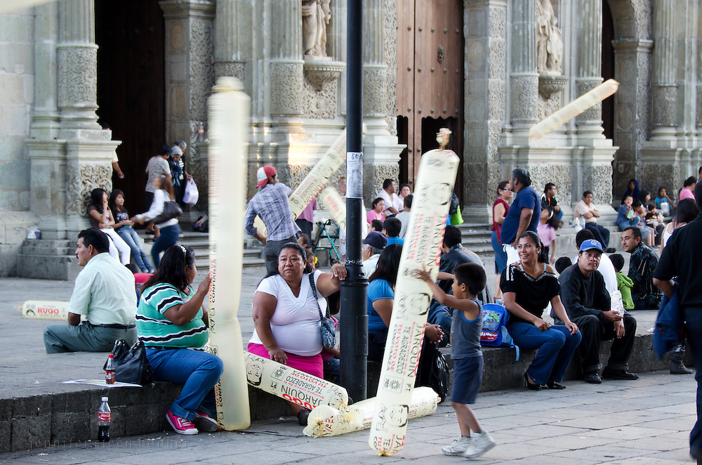 Children play with inflatable political advertising toys as adults talk and watch the street life in the Zócalo, Oaxaca, Mexico.