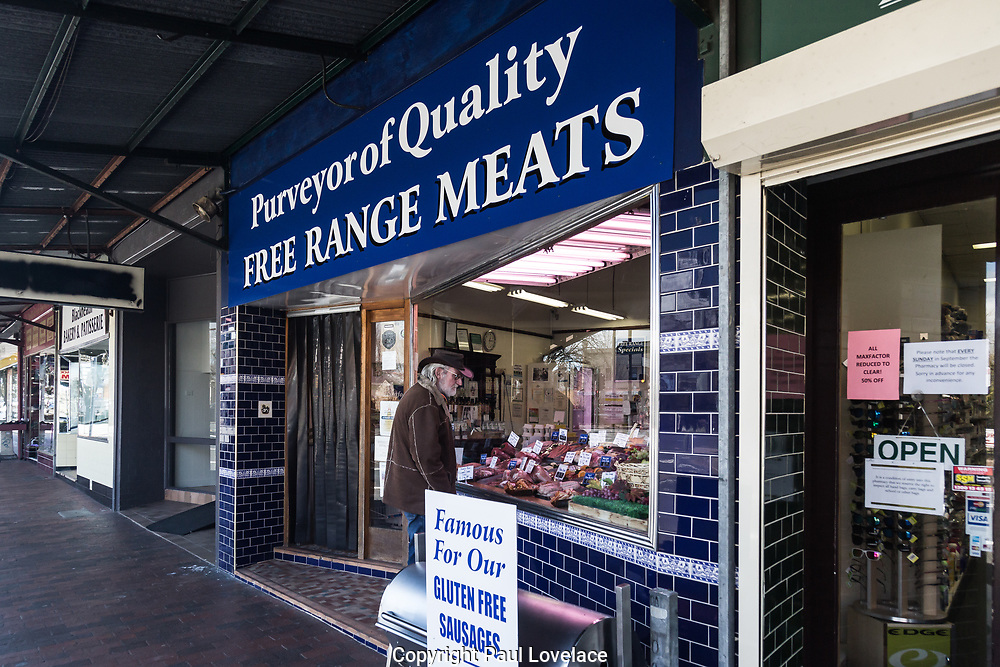 A local man looks in the window of a butchers shop wearing an Australian cowboy hat, Blackheath, The Blue Mountains, NSW, Australia.