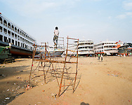 A boy climbs on a metal scaffolding structure in Keraniganj shipyard. The dockyards employ over 15,000 workers, some underaged, with salaries often below $5 a day; they break down massive shipping vessels as well as create new ships from the parts. Most of the workers come from the rural parts of Bangladesh to work in underpaid, harsh and dangerous conditions.