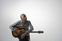 Young pensive man holding guitar