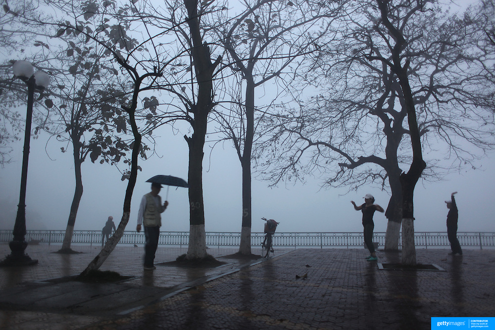 A women's keep fit class on a wet misty morning beside Ho Tay Lake, Hanoi. Vietnam.. For a county not know for it's sporting prowess, Hanoi, Vietnam's capital, appears to be gripped in a fitness frenzy. Before 6am street corners, parks and lake sides are a hive of activity as keep fit classes, Tai chi and personal exercise regimes are seen in abundance around the city. Particularly noticeable are Women's keep fit classes, often accompanied by loud poor quality western disco beat music as the occupants of the city get fit come rain or shine. Hanoi, Vietnam. 17th March 2012. Photo Tim Clayton
