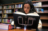 Young woman researching in university library.