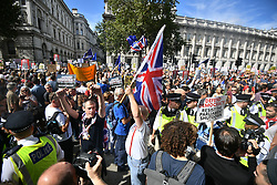 © Licensed to London News Pictures. 31/08/2019. London, UK. A group of Brexit supporters walk through the pro EU demo. Protestors gather near 10 Downing Street in Westminster, central London to demonstrate as part of a nationwide 'Stop The Coup' day of action against Boris Johnson's plans to suspend parliament. More than 80 demonstrations are planned across the UK in response to government plans to prorogue parliament. Photo credit: Ben Cawthra/LNP