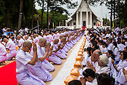 19 JULY 2014 - KHLONG LUANG, PATHUM THANI, THAILAND: Men being ordained as monks pray and thank people presenting them with their robes during a mass ordination at Wat Phra Dhammakaya. Seventy-seven men from 18 countries were ordained as Buddhist monks and novices at Wat Phra Dhammakaya, a Buddhist temple  north of Bangkok, Saturday. It is the center of the Dhammakaya Movement, a Buddhist sect founded in the 1970s and led by Phra Dhammachayo (Phrathepyanmahamuni). It is the largest temple in Thailand. The Dhammakaya sect has an active outreach program that attracts visitors from around the world.    PHOTO BY JACK KURTZ
