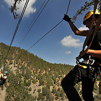 Navitat Marketing Manager Caley Bowman, left,  crosses Buford Canyon on a zip line as Canopy Guide Chris Gearhart watches the line. Guides take visitors on a high-adventure through the tree tops via a fast-moving zip line experience in the  Angeles National Forest near Wrightwood, Wednesday, July 7, 2011. (Eric Reed/Photographer)