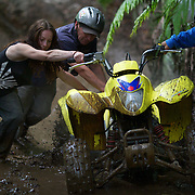Participants push a quad bike out of the mud on a quad bike course near Taupo with Taupo Quad Bikes. Taupo, Noth Island, New Zealand. 7th January 2011. Photo Tim Clayton.