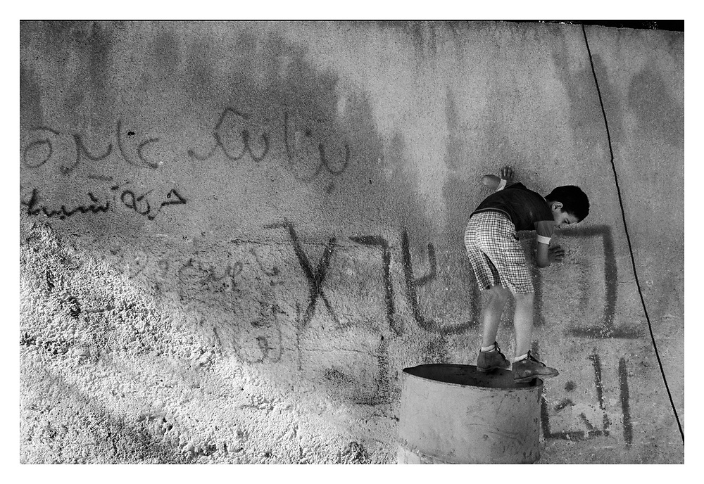 A young boy playing by the separation wall in the Aida refugee camp. Bethlehem, Palestine, 2007
