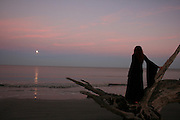Witchy woman watches moonrise over the ocean at sunset.