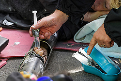 © Licensed to London News Pictures. 10/10/2019. London, UK. Police attempt to debond the hands of two Extinction Rebellion activists glued together in a plastic tube on the road surrounding Trafalgar Square in Westminster, central London where they have been demonstrating for a fourth day running. The climate change group have blockaded the Westminster area, demanding that the government takes immediate and decisive action on climate change. Photo credit: Ben Cawthra/LNP