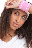 Portrait of tired young woman with hand on head against white background