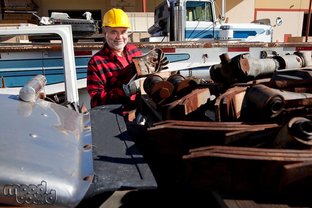 Worker sorting scrap metal in front of Cargo truck