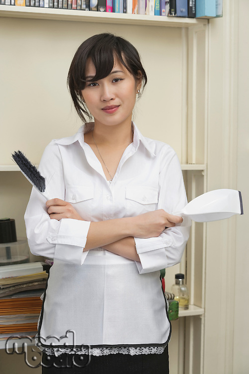 Portrait of young female housekeeper holding brush and dustpan