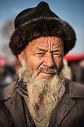 A Uyghur man poses for his photo in the Shufu County Bazaar near Kashgar in Xinjiang, China. Most older Uyghur men keep their hair shaved short and beards long. They typically wear handmade hats to keep warm. There are bazaars everyday in Xinjiang, but special days like Sunday are more eventful. Anything can be purchased from livestock to cosmetics.