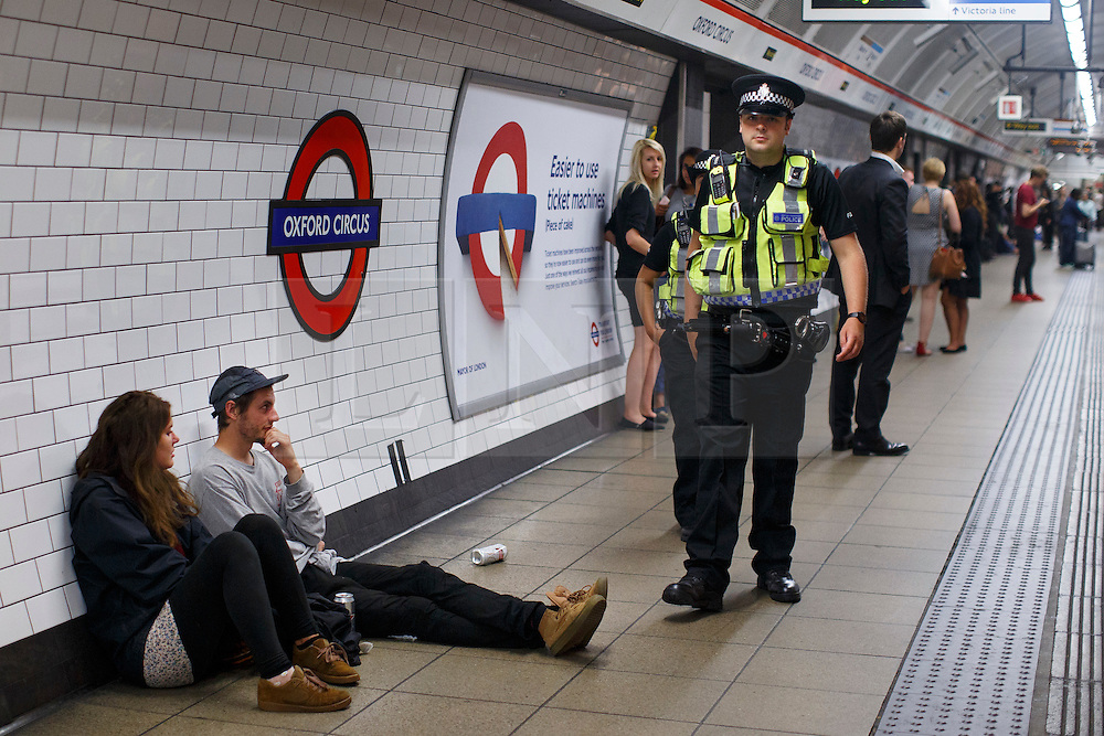 © Licensed to London News Pictures. 20/08/2016. London, UK. British Transport Police officer patrols at Oxford Circus station during the night tube service for the first time on 20 August 2016. Transport for London started a 24-hour Tube service on Victoria and Central lines as demand has soared over recent years, with passenger numbers on Friday and Saturday nights up by around 70 per cent since 2000. The plan was announced in November 2013 and intended to begin in September 2015, but strikes over pay delayed the start by nearly another year. Photo credit: Tolga Akmen/LNP