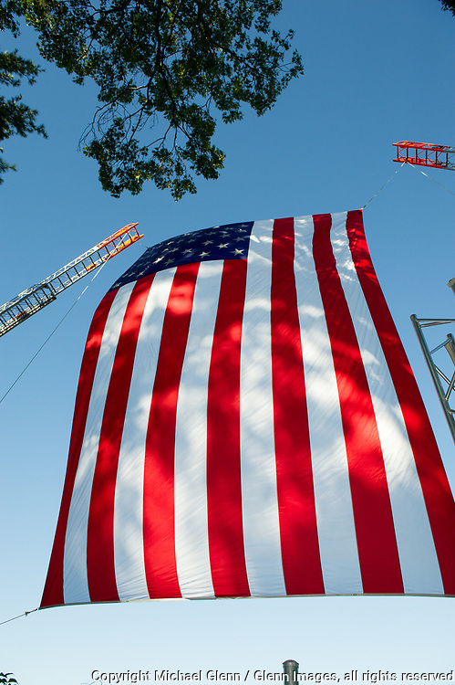 1 Oct 2017 Elmont, New York United States of America // Large US Flag suspended between 2 Ladder trucks at the 3RD annual national stair climb for fallen firefighters at the Belmont Park racetrack  Michael Glenn  /   for the FDNY