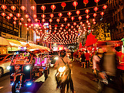 """07 FEBRUARY 2016 - BANGKOK, THAILAND:  Chinese New Year lanterns hang over people on Yaowarat Road, the heart of Bangkok's Chinatown. Chinese New Year, also called Lunar New Year or Tet (in Vietnamese communities) starts Monday February 8. The coming year will be the """"Year of the Monkey."""" Thailand has the largest overseas Chinese population in the world; about 14 percent of Thais are of Chinese ancestry and some Chinese holidays, especially Chinese New Year, are widely celebrated in Thailand.        PHOTO BY JACK KURTZ"""