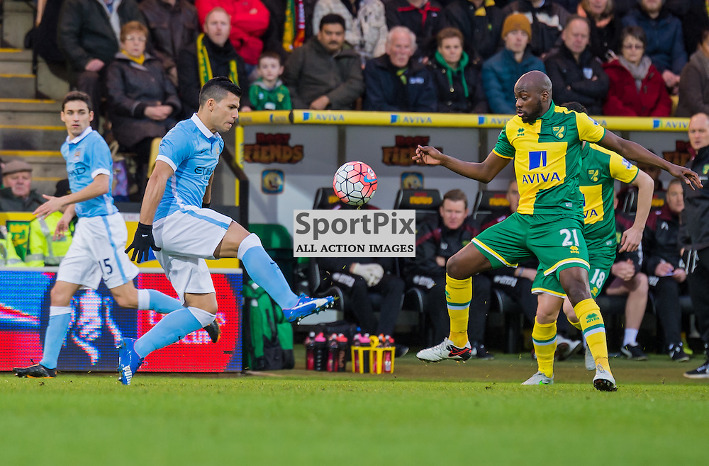 Manchester City forward Sergio Aguero (10) and Norwich City midfielder Youssuf Mulumbu (21) challenge for a loose ball in midfield