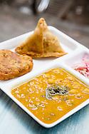 A plate of mixed Indian vegetarian street food: vegetarian cutlet, samosa and channa masala. Colaba, Mumbai, India
